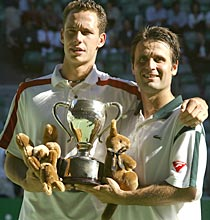 Michael Llodra (left) and Fabrice Santoro hold up the men's doubles trophy