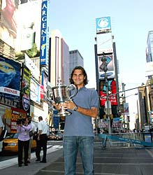 Roger Federer poses with his 2004 US Open trophy at Times Square in New York