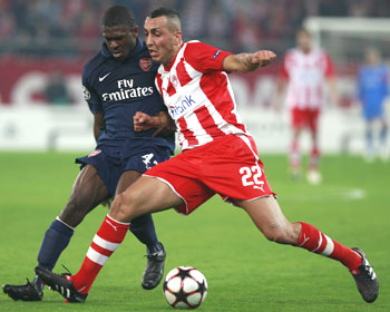 Kostas Mitroglou of Olympiakos (right) and Kerrea Gilbert of Arsenal vie for possession