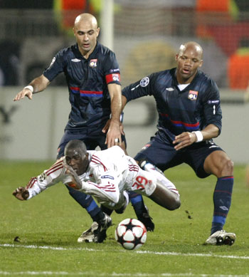 Debrecen's Adamo Coulibaly takes a tumble after being challenged by Olympique Lyon's Cris (left) and Jean-Alain Boumsong