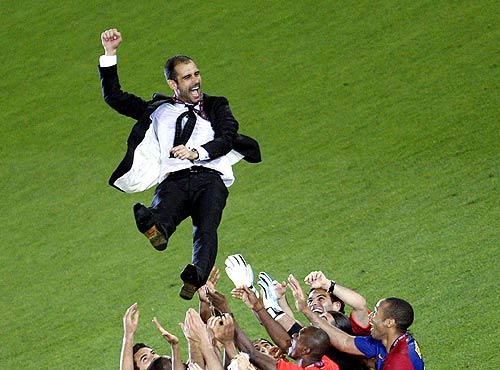Barcelona's coach Pep Guardiola is chaired by his players