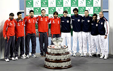 Members of Serbian and French tennis teams pose with the Davis Cup trophy after the official draw at Belgrade Arena
