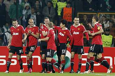 Manchester United players celebrate after scoring a goal