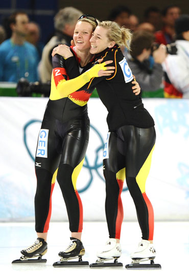 Germany's Stephanie Beckert (left) is embraced by team-mate Anna Friesinger-Postma after winning the women's speed skating team pursuit event