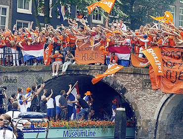 Fans cheer as they welcome the Dutch team back home during a canal parade in Amsterdam