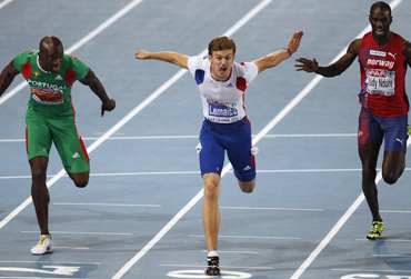 France's Lemaitre (centre) crosses the finish line to win the men's 100 metres final in the European Athletics Championships