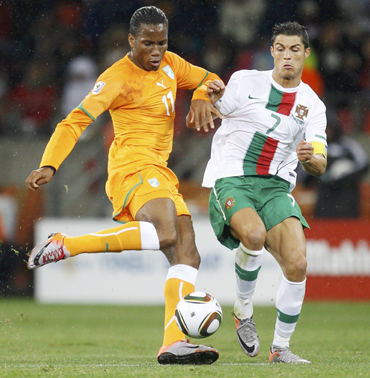 Ivory Coast's Didier Drogba fights for the ball with Portugal's Cristiano Ronaldo during their 2010 World Cup