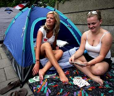 Fans play cards while waiting in the queue for tickets