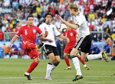 England's Frank Lampard (left) tries to score past German defenders