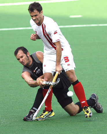 New Zealand's Blair Hopping (left) blocks Canada's Philip Wright as their vie for possession