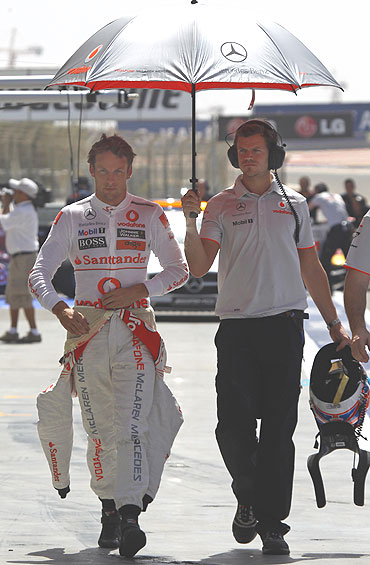 Jenson Button (left) walks in the pits