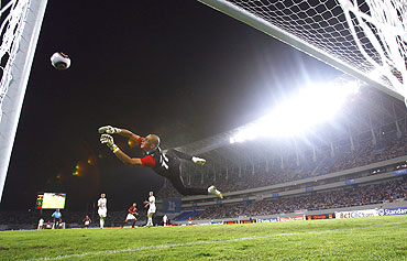 Algeria's goalkeeper Faouzi Chaouchi dives as Egypt's Emad Moteab takes a penalty shot during their African Nations Cup semi-final