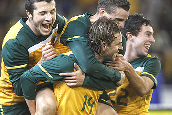 Australia's Brett Holman (centre) celebrates with team-mates Nikita Rukavytsya (left) and Jason Culina (top) after scoring against New Zealand during their international friendly