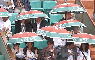 Spectators shelter themselves from the rain with umbrellas during the French Open tennis tournament at Roland Garros in Paris