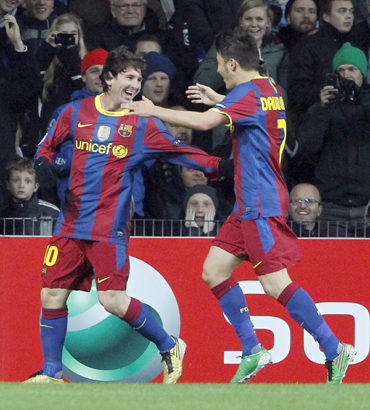 Barcelona's Lionel Messi celebrates with teammate David Villa after scorong against FC Copenhagen on Tuesday