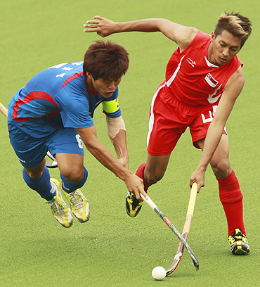 Mohamed Ishak Ismail of Singapore (right) challenges Lee Nam-yong of South Korea during their hockey match on Sunday