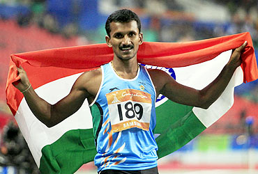 India's Joseph Ganapathiplackal Abraham celebrates winning the men's 400m hurdles final at the 16th Asian Games in Guangzhou