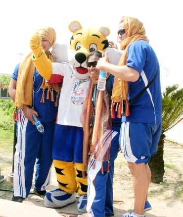 Athletes from Tuvalu pose with Sheru the mascot