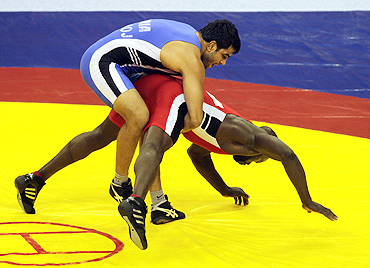 Manoj Kumar (blue) challenges Nigeria's Joe Agbonavbare during their 84 kg men's wrestling bout