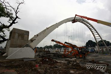 A crane removes the rubble of the collapsed bridge at the J N Stadium