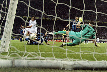 Schalke 04's Raul Gonzalez (left) scores past Inter Milan's goalkeeper Julio Cesar (right) and Andrea Ranocchia (2nd from left)