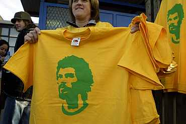 Fans hold tee shirts depicting Brazilian football legend Socrates