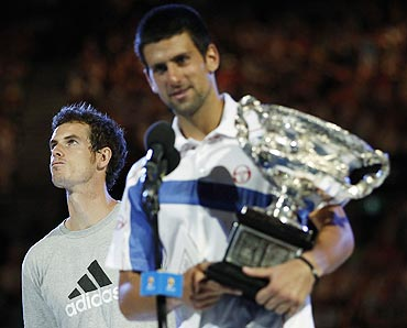 Andy Murray looks away as Novak Djokovic of Serbia holds his trophy