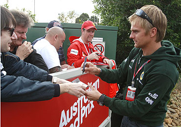 Lotus Formula One driver Heikki Kovalainen of Finland signs autographs