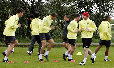 Manchester United's players warm up during a practice session at the club's Carrington training ground in Manchester