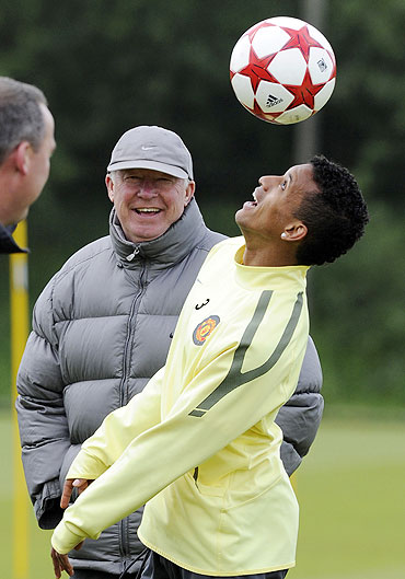 Manchester United's Nani (right) heads the ball as coach Alex Ferguson looks on