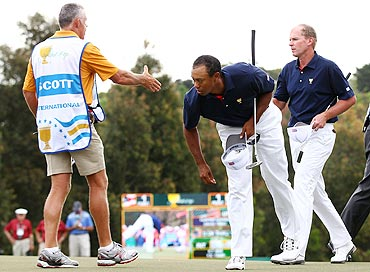 Tiger Woods looks on as Steve Williams, caddie to Adam Scott (not pictured), shake hands with Steve Stricker