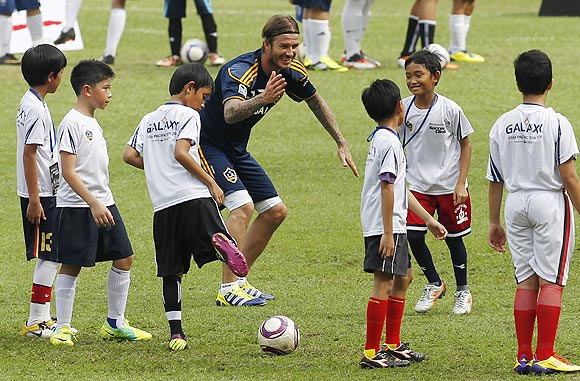 Los Angeles Galaxy's David Beckham (centre) interacts with kids during a coaching clinic at Bung Karno stadium in Jakarta