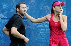 Daniela Hantuchova of Slovakia and golfer Sergio Garcia look on after they hit balls together on a practice court in New York on Wednesday