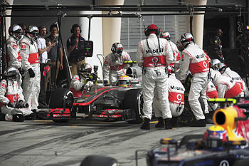 Mechanics work in the car of McLaren Formula One driver Lewis Hamilton of Britain as he pits during the Bahrain F1 GP on Sunday