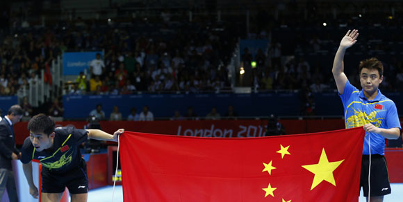 China's Zhang Jike bows as compatriot Wang Hao waves as they celebrate with a Chinese flag after their men's singles gold medal table tennis match