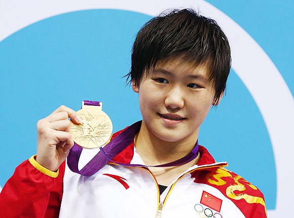 China's Ye Shiwen poses with her gold medal after winning the women's 200m individual medley final on Monday