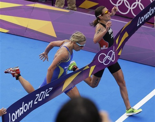 Switzerland's Nicola Spirig, right, finishes ahead of Sweden's Lisa Norden to win the gold medal in the women's triathlon