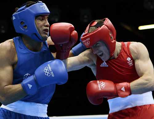 Manoj Kumar of India, left, and Thomas Stalker of Great Britain, fight during the men's light welterweight boxing competition