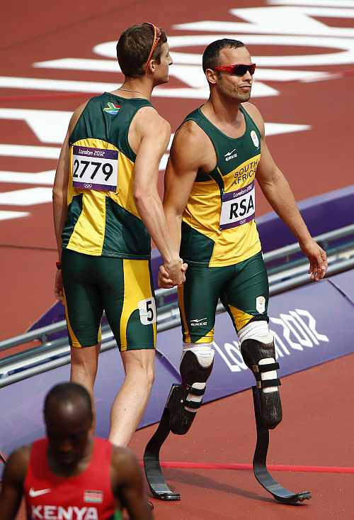 South Africa's Oscar Pistorius and Willem de Beer react after their team did not finish in the men's 4x400m relay round 1 heat