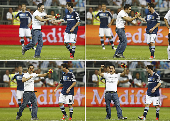 A combination of four pictures shows a pitch invader meeting Argentina's Lionel Messi during the friendly soccer match against Germany in Frankfurt on Wednesday