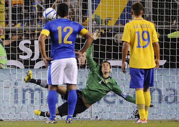 Brazil's Pato (unseen) scores a penalty kick past Sweden's goalkeeper Andreas Isaksson