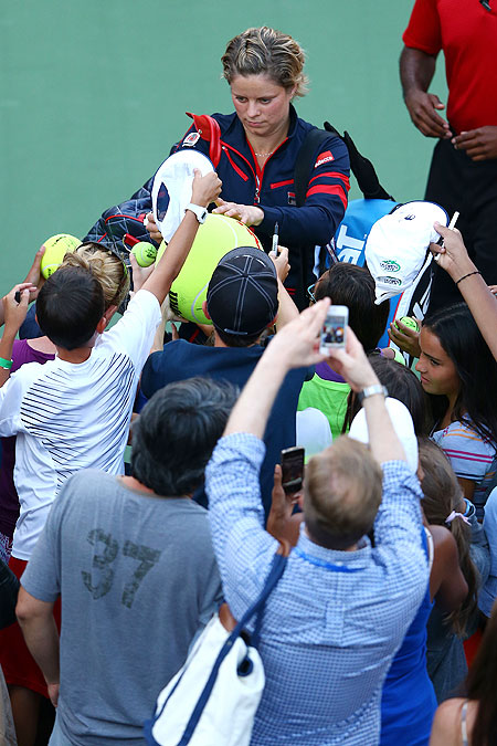 Kim Clijsters of Belgium signs autographs for fans as she leaves the court following her defeat to Laura Robson of Great Britain