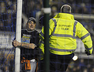 A man (left) handcuffs himself to the goalpost during the English Premier League soccer match between Everton and Manchester City