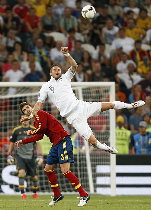 France's Olivier Giroud (right) challenges Spain's Gerard Pique