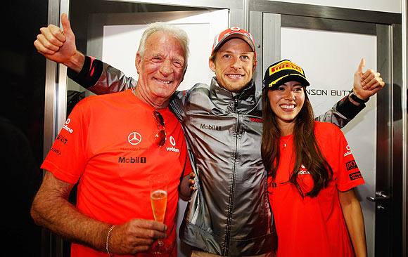 Jenson Button celebrates his victory with father John and girlfriend Jessica Michibata