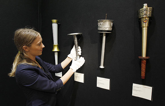 A Christie's employee poses for a photograph with a selection of Olympic torches at the art gallery in London. The torches, which are from the 1980 Moscow Olympics (left), the 1936 Berlin Olympics (2nd from left), the 1948 London Olympics (2nd right) and the 1988 Seoul Olympics were auctioned last month
