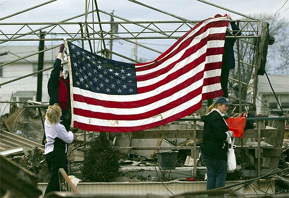 People raise the American flag among the wreckage of their homes