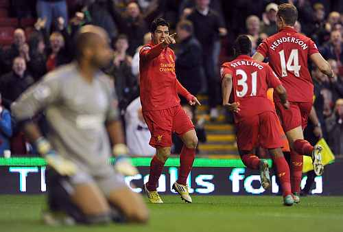 Luis Suarez of Liverpool celebrates scoring with team-mates Raheem Sterling and Jordan Henderson as Ali Al Habsi of Wigan Athletic looks dejected during the Barclays Premier League match