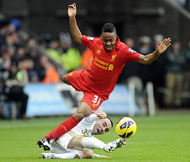 Swansea City's Leon Britton challenges Liverpool's Raheem Sterling (top) during their English Premier League match at the Liberty Stadium in Swansea, on Sunday