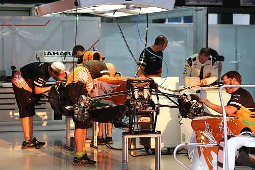 The mechanics work on the Force India car